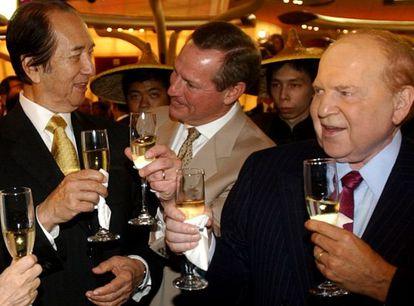 Ho (corbata dorada) y Adelson (corbata morada) brindan tras la apertura de un casino del segundo en Macao en 2004.