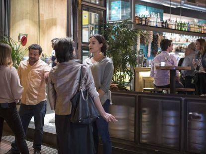 Un grupo de jóvenes fuma a las puertas de un local en la calle de Ponzano, en Madrid.