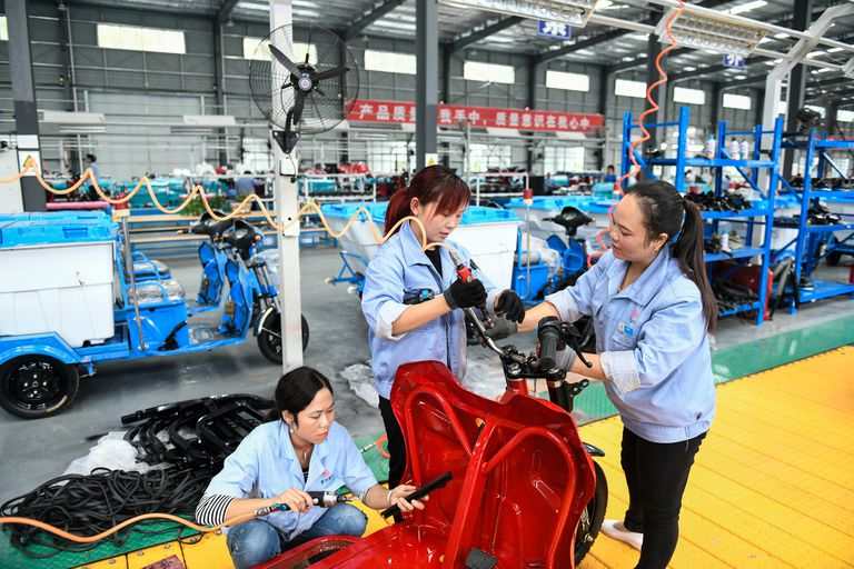 Empleados en una cadena de producción de motocicletas eléctricas en Qinglong, en la provincia china de Guizhou.