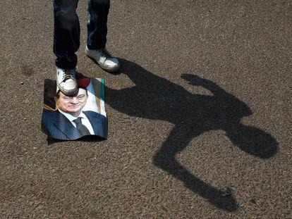 Un opositor al exdictador egipcio Hosni Mubarak pisa una fotografía del 'rais' frente a la academia de policía de El Cairo, donde es juzgado.
