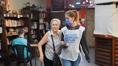 Una voluntaria de la Universidad de Buenos Aires acompaña a una mujer mayor durante una jornada de la campaña de vacunación en la capital de Argentina.