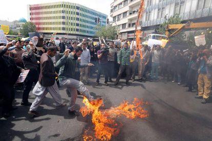 Iraníes queman una bandera de EE UU en una protesta este viernes en Teherán