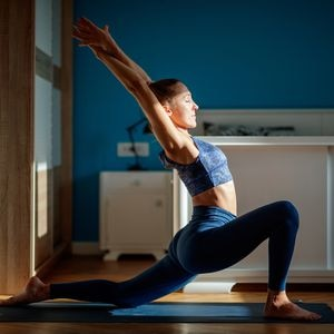 Young attractive woman practicing low lunge pose at home, stretching in Anjaneyasana exercise