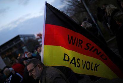"""Un simpatizante de AfD lleva una bandera donde se lee """"Nosotros somos el pueblo"""" en una marcha en Erfurt en marzo de 2020."""