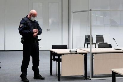 Un agente consulta su reloj en el juzgado de Itzehoe, donde este jueves comenzaría el juicio de la mujer de 96 años, que era secretaria del comandante de las SS en el campo de concentración de Stutthof.
