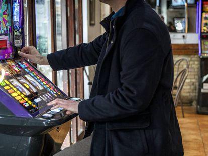 Un hombre echa una moneda a una máquina tragaperras en un bar de Valencia.
