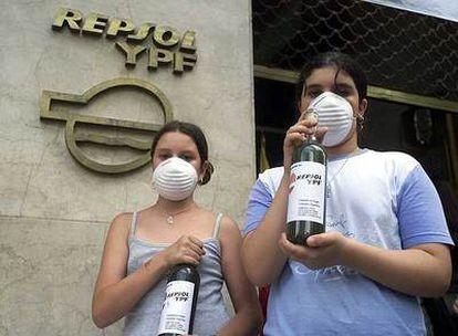 Activistas muestran botellas de agua contaminada en la sede de Repsol en Buenos Aires.