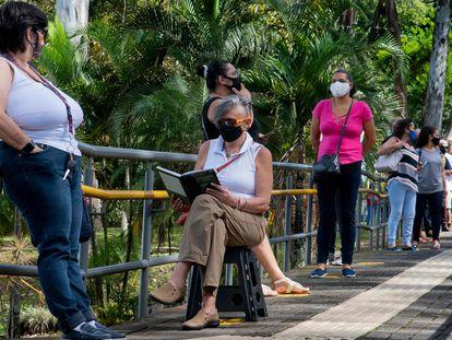Varias personas hacen una fila en un centro de salud mientras esperan ser vacunadas contra la covid-19 en San José, Costa Rica.