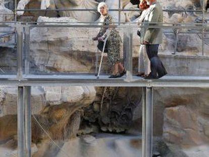 Tres visitantes pasean por el puente sobre la Fontana de Trevi.