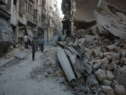 Sirios miran un edificio bombardeado de un barrio opositor de Alepo, este domingo.