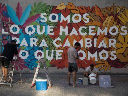 El colectivo Boa Mistura realiza una intervención artística en la fachada del Centro Dramatico Nacional, en Lavapiés (Madrid).