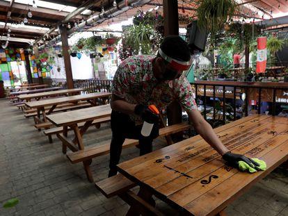 Un mesero limpia una mesa mientras espera la reapertura del restaurante Comedor de los Milagros en Ciudad de México.