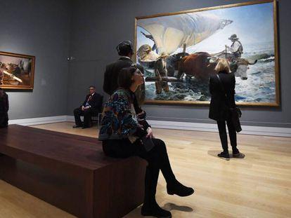 Visitantes en la muestra de Sorolla en Londres observan 'La vuelta de la pesca' (1894), a la derecha, y 'Encajonando pasas' (1901). En vídeo, la Reina Letizia durante la inauguración de la exposición.
