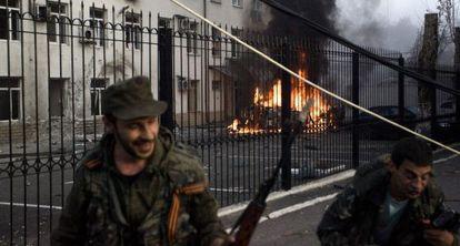 Separatistas prorrusos se alejan de un carro ardiendo en Donestk.
