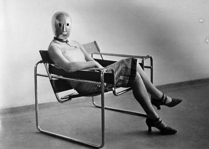 Una estudiante posa con una máscara del Ballet Triádico, de Oskar Schlemmer, sentada en la silla Wassily, de Marcel Breuer, en los años 20.