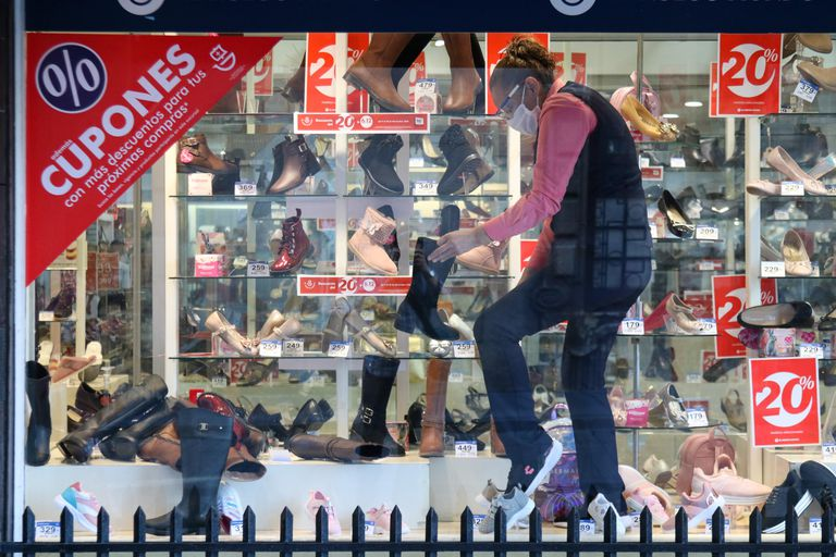 Vendedores colocan anuncios de El Buen Fin en sus tiendas, en Ciudad de México.