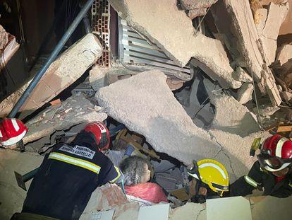 Los bomberos rescatan con vida a una de las tres personas sepultadas.