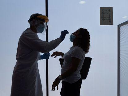 Un enfermero toma muestras a una mujer en un centro médico de Zaragoza para realizarle una prueba de coronavirus.