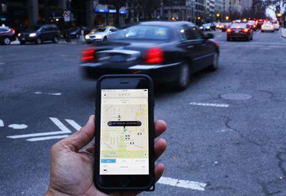 Un hombre muestra la aplicación Uber en su móvil en Washington (EE UU).