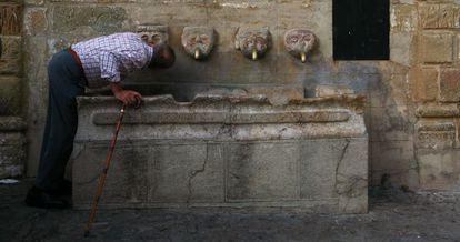 Un vecino de Grazalema bebe de una fuente pública.