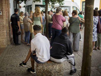 Dos menores fugados del centro de acogida Hogar San Juan de Ávila esperan en la puerta a ser readmitidos.