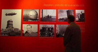 Un visitante mira las fotografías de los primeros viajes en dirigible en España.