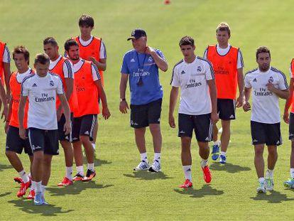 Ancelotti, en el centro, rodeado de los jugadores del Madrid en el entrenamiento de ayer.