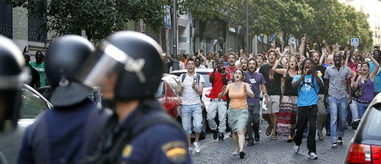 Un momento de la protesta, en la que vecinos de Lavapiés y miembros del 15-M hacen frente a los antidisturbios en Lavapiés.