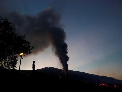 Un hombre observa como el volcán emite grandes columnas de ceniza y dióxido de azufre desde Tajuya, al norte del cono principal este domingo.