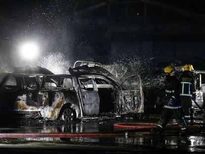 Tres bomberos apagan un incendio ocasionado durante las protestas de la noche del 14 de julio en Santiago de Chile.