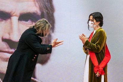 """El artista Nacho Cano entrega a Isabel Díaz Ayuso la gran cruz del Dos de Mayo después de que esta le condecorara en la sede de la Comunidad. """"Por ser tan buena presidenta, la medalla te la mereces tú"""", le dijo."""