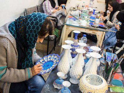 Azin en la cooperativa Tolou' de Isfahán (Teherán), en la que trabaja junto con otras mujeres, en el momento de esmaltar un plato.