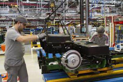 Dos operarios colocan las baterías de una furgoneta en la cadena de montaje de la planta de PSA. EFE/Archivo
