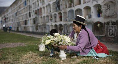 Una mujer adorna con flores la tumba de un familiar.