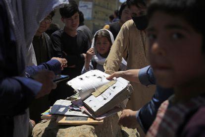 Varios afganos muestran algunas de los cuadernos y libros de las víctimas del atentado junto a un colegio de Kabul, el domingo.