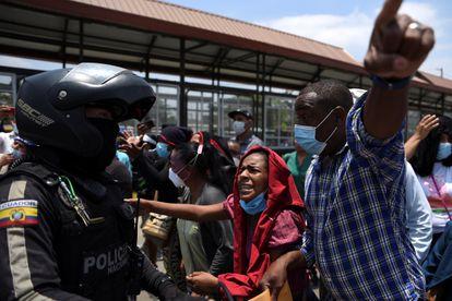 I parenti dei prigionieri chiedono informazioni su di loro agli agenti di polizia della prigione di Guayaquil.