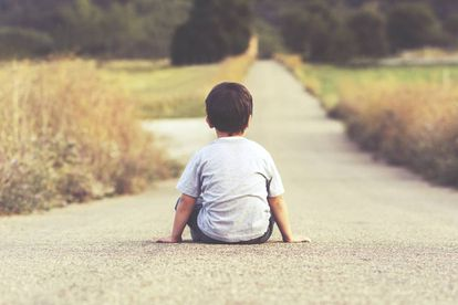Un niño mira el horizonte.