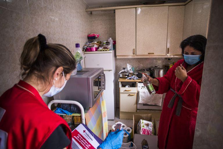 Sofía, voluntaria de Cruz Roja (izquierda), reparte alimentos en el piso en que vive Mari Cruz (derecha), en San Sebastián de los Reyes (Madrid).
