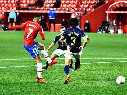 El delantero colombiano del Granada Luis Suárez intenta un lanzamiento ante dos rivales de Osasuna, durante el partido de LaLiga este martes en el estadio Nuevo Los Cármenes de Granada.