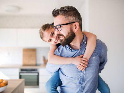 Un padre lleva a hombros a su hija en casa.