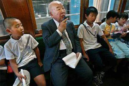 Tatsuo Sora, un superviviente de 77 años, cuenta su experiencia a un grupo de niños desde uno de los tranvías que sobrevivieron a la bomba en Hiroshima.