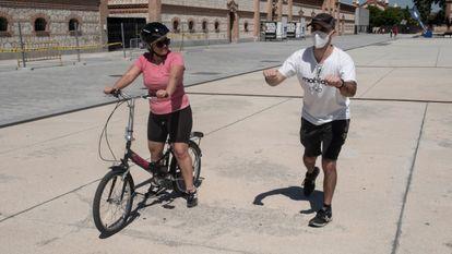 El profesor José Antonio Loma enseña a una alumna la postura para empezar a montar en bici, el sábado en Matadero.