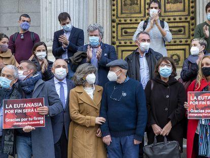 La diputada socialista María Luisa Carcedo (en el centro) con activistas que apoyan la regulación de la eutanasia y varios diputados, este jueves a las puertas del Congreso.