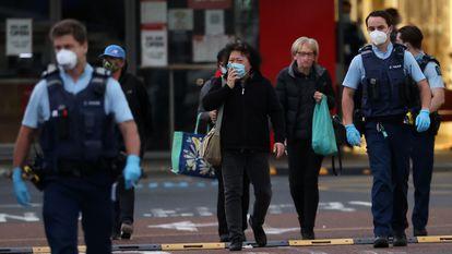 La policía escolta a varios transeúntes en la calle donde fue perpetrado el ataque, poco después de producirse.