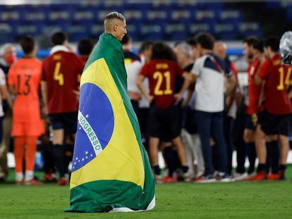 Richarlison, enfundado en una bandera de Brasil mientras los jugadores españoles hacen un corro.