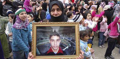Una manifestante contra El Asad muestra la foto de un desaparecido.