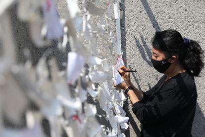 Una mujer coloca un mensaje dedicado a las personas fallecidas por la covid-19, en un mural en Ciudad de México el pasado sábado.