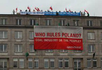 """Activistas de Greenpeace despliegan desde el tejado del Ministerio de Economía pancartas con el mensaje """"¿Quién gobierna Polonia? ¿La industria del carbón o el pueblo?"""", durante una protesta, hoy, en Varsovia (Polonia)."""