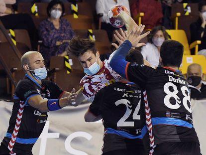 Pérez de Arce, de Ademar, ataca la defensa del Sinfín el pasado sábado en el primer partido de élite en España con mascarillas.