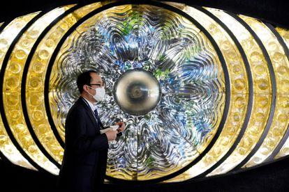 Un hombre protegindo con una mascarilla pasa ante la obra de arte 'Eye of Shinjuku' en la estación de Shinjuku en Tokio, Japón,